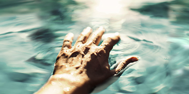 Soft focus of hand touching water to create ripple effect